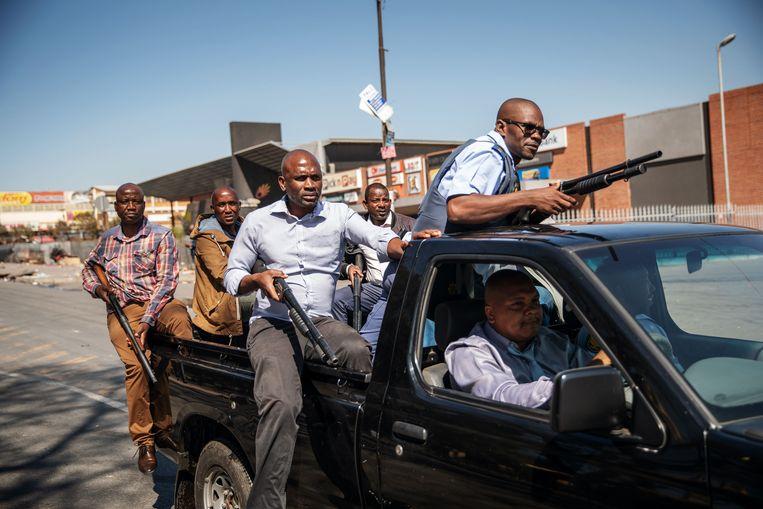 South African Police Service-agenten in burger patrouilleren na de plunderingen in Johannesburg.  Beeld AFP