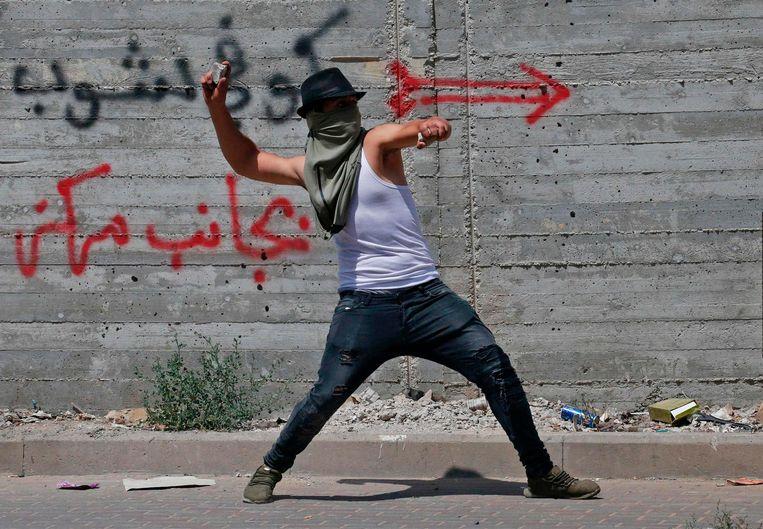 Een Palestijnse man gooit stenen naar Israëlische agenten tijdens een protest in Hebron. Beeld afp