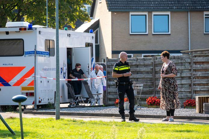 Terwijl een agent met een buurvrouw spreekt, maken forensisch onderzoekers zich klaar om het huis verder uit te kammen.