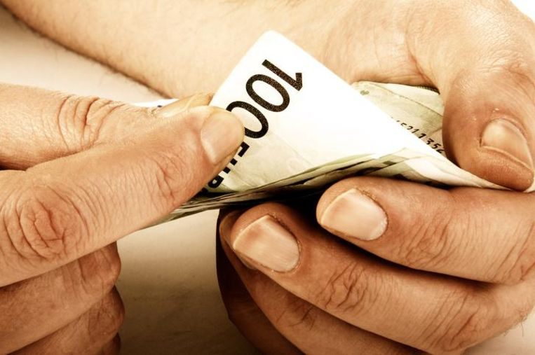 Workers hands counting hundred euro banknotes, sepia toned image