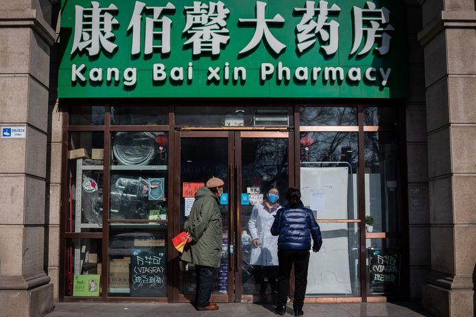 Des personnes portant un masque devant une pharmacie de Pékin, le 15 février 2020.