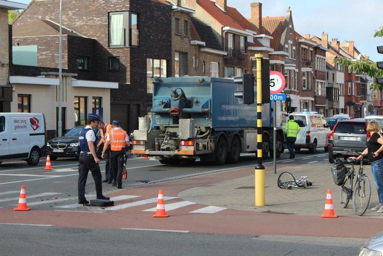 De verwrongen fiets ligt op het voetpad nabij de vrachtwagen. Een agent staat bij de fietstas van de vrouw.