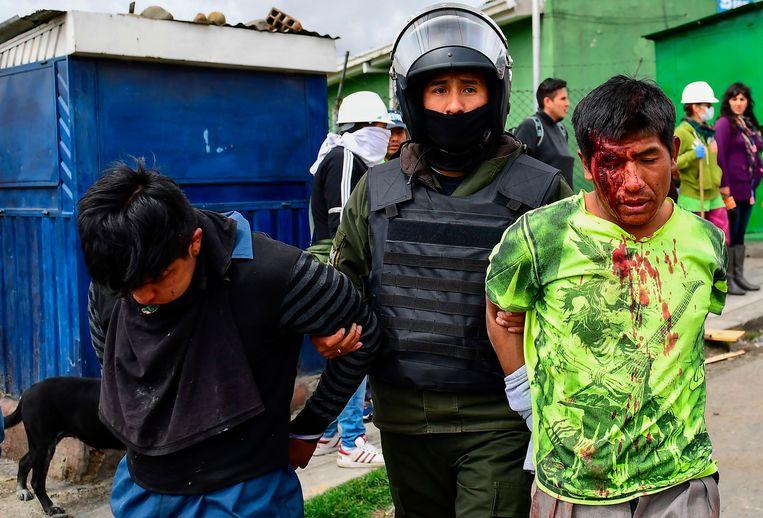 Een politieman arresteert twee aanhangers van voormalig president Evo Morales in La Paz op 11 november, 2019.   Beeld AFP