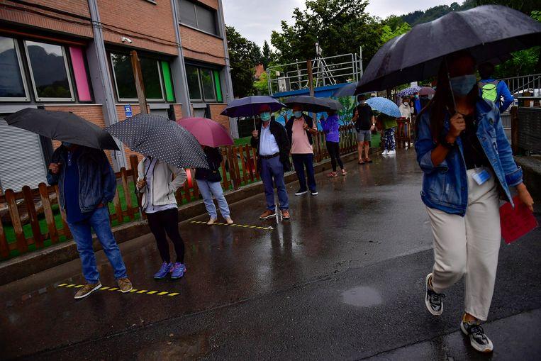 In het dorp Durango staan de mensen in de rij re wachten om te mogen stemmen. Ze dragen verplicht gezichtsmaskers om verspreiding van het coronavirus te voorkomen. De Baskische autoriteiten namen speciale maatregelen tijdens de regionale verkiezingen. Beeld AP