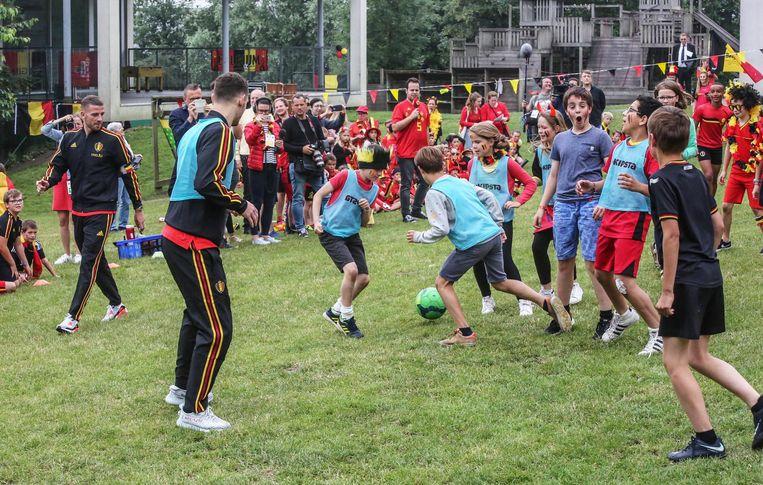 Alderweireld en Vermaelen spelen voetbal met de leerlingen.