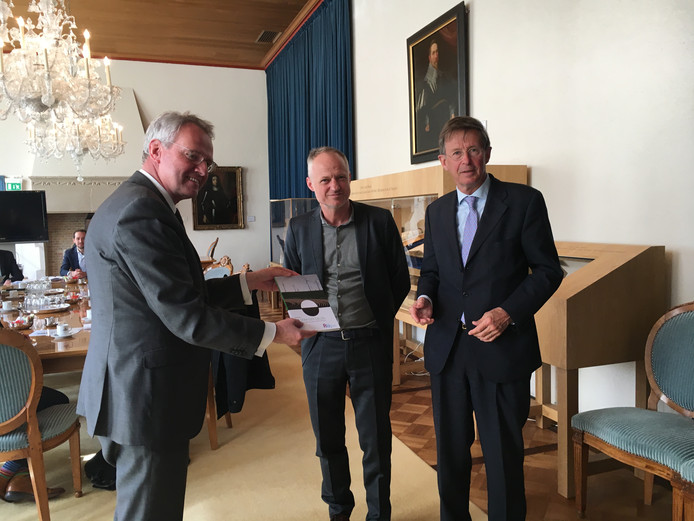 Commissaris van de koning Han Polman (l) ontvangt het rapport De som der delen uit handen van Co Verdaas en Jan Jaap de Graeff (r) van de Raad voor de leefomgeving en infrastructuur.