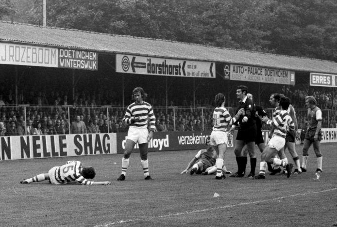 Henk Overgoor (nummer 5) heeft in de legendarische thuiswedstrijd van De Graafschap tegen Feyenoord (5-7 in oktober 1973) zijn kauwgom ingeslikt en ligt op de grond. Guus Hiddink, die net daarvoor Feyenoorder Henk Wery onderuit heeft geschoffeld, komt poolshoogte nemen.