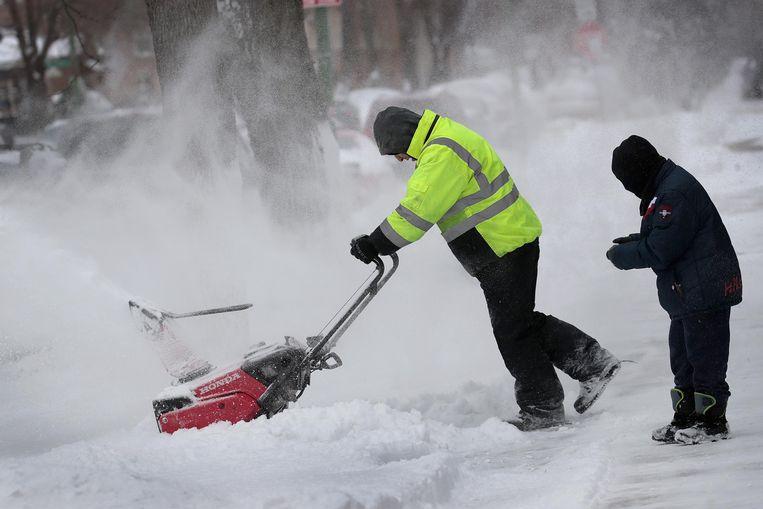 In Chicago probeert een man met een sneeuwruimer de weg begaanbaar te maken. In de stad en omgeving viel tussen de 10 en 25 centimeter sneeuw.