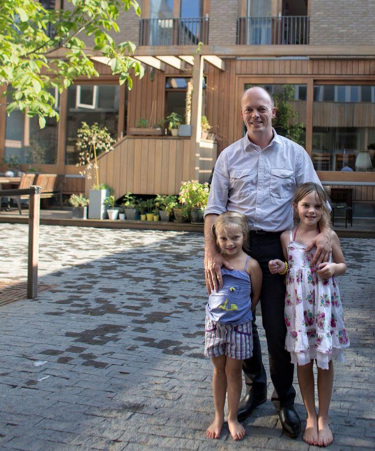 Niels Bon met zijn dochters Vera (L) en Jasmijn (R) bij hun woning aan de Lijnbaansstraat. Beeld Rink Hof