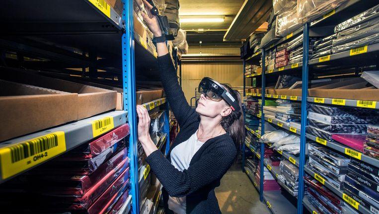Een medewerker van Montapacking in Molenaarsgraaf wordt door de Hololens door het distributiecentrum geleid Beeld Adrie Mouthaan
