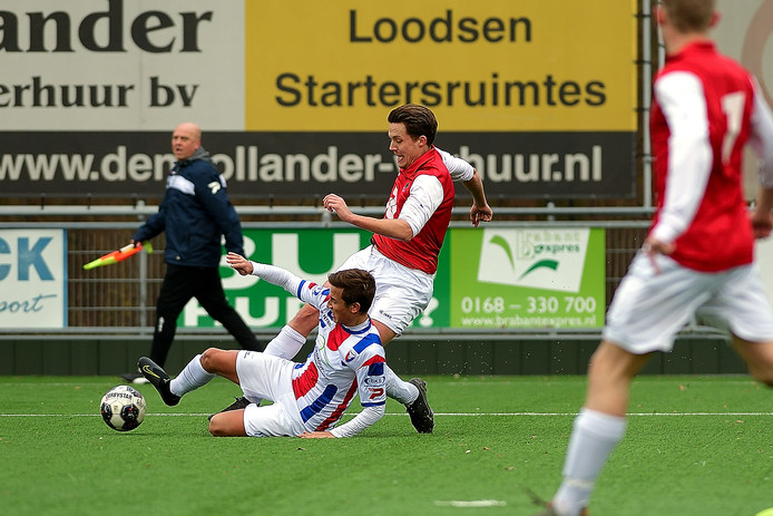 Janko Raaijmakers (midden) komt er niet aan te pas tegen Klundert-verdediger Rijk van de Reijt (links).