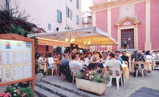 Tegen de avond, wanneer de grootste warmte verdwenen is, vullen de pleintjes in Calvi zich met eetlustigen.