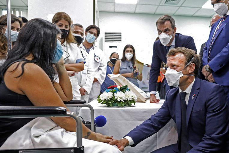 President Macron (geknield) bezoekt opnieuw slachtoffers van de giga-explosie in Beiroet. Deze keer in het Rafik Hariri University Hospitalin, achter hem de Franse minister van Volksgezondheid, Olivier Veran.   Beeld AFP