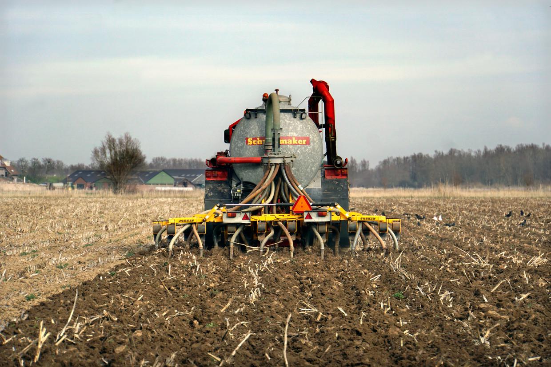Een loonwerker rijdt met een tractor over het land om mest in de grond te injecteren.