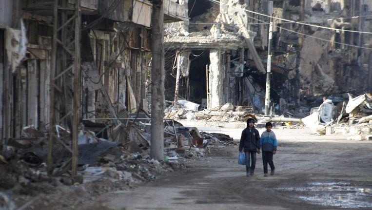 Twee kinderen lopen door Deir ez-Zor, een stad in Syrië Beeld ANP