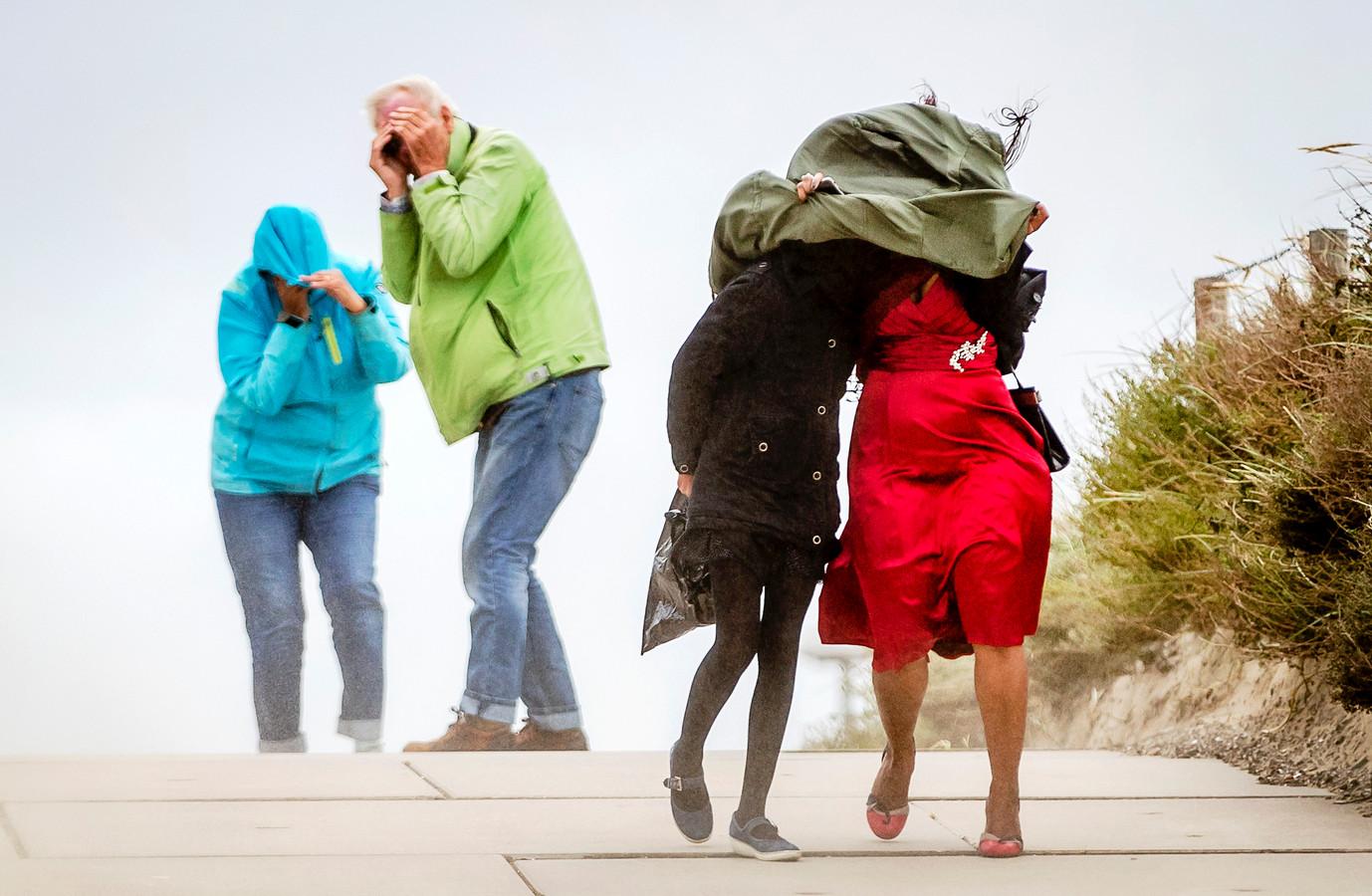 Mensen trotseren de storm op het strand van IJmuiden.