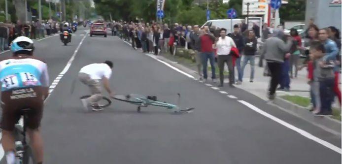 Een man raapt de fiets snel op en zo kunnen de renners doorrijden.