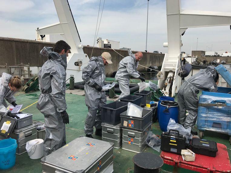 De onderzoekers dragen beschermende pakken om niet in contact te komen met giftige stoffen.