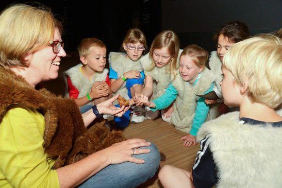 Enkele leerlingen kijken met veel interesse naar een voorwerp uit het museum.
