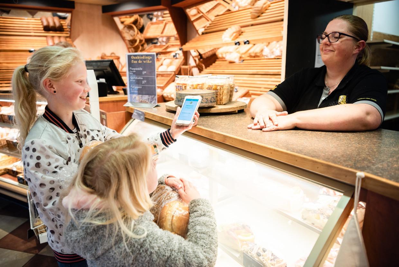 Twee zusjes halen met hun moeder (buiten beeld) bij Bakkerij de Groot in Stiens een op TooGoodToGo geplaatste zak met brood en gebak op.  Beeld Katja Poelwijk