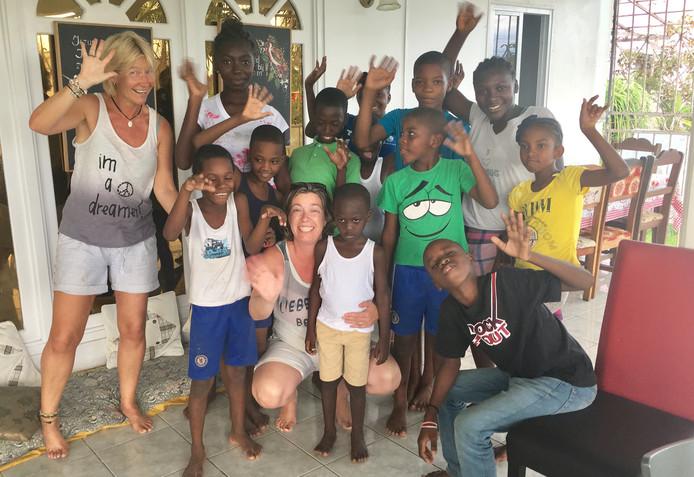 Martine Wakkee (links) tussen de kinderen van Mama Joyce in het tehuis in Paramaribo.