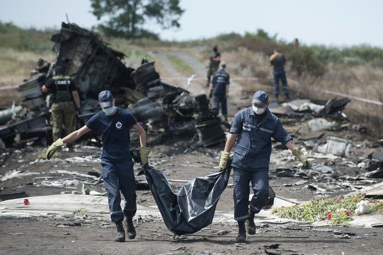 Reddingswerkers dragen het lichaam van een slachtoffer. Beeld null