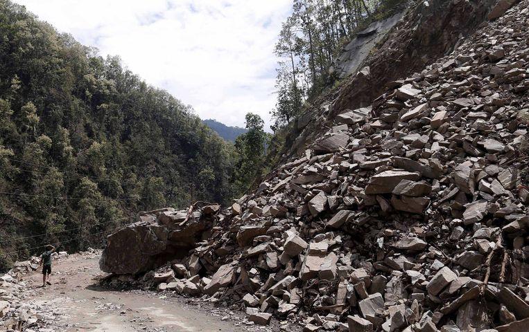 Een jongetje loopt langs een door stenen geblokkeerde weg in Nepal. Beeld epa
