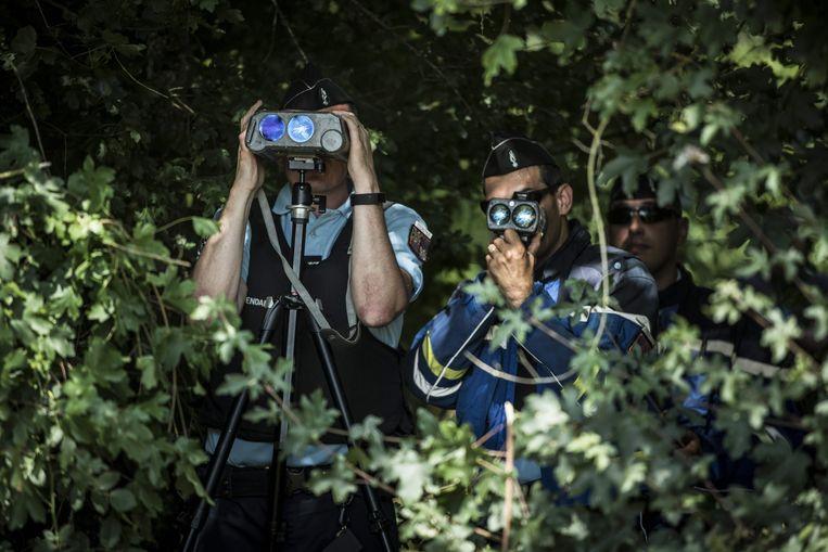 Franse politieagenten kijken door een camera die de snelheid van voorbijrazende voertuigen detecteert naar de weg.