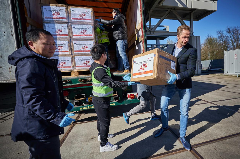 Minister Hugo de Jonge neemt de eerste doos met mondkapjes in ontvangst van Steven Cai (Huawei). Het telecommunicatiebedrijf doneert 800.000 mondmaskers.