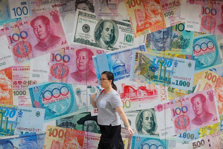 Een vrouw wandelt langs een wisselkantoor in Hongkong. Beeld AP