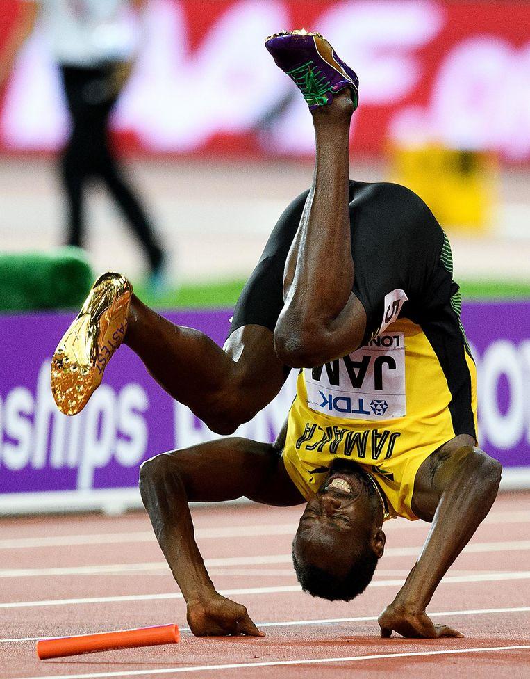 Bolt scheurt zijn hamstring, maakt een koprol en belandt op de baan. Beeld getty