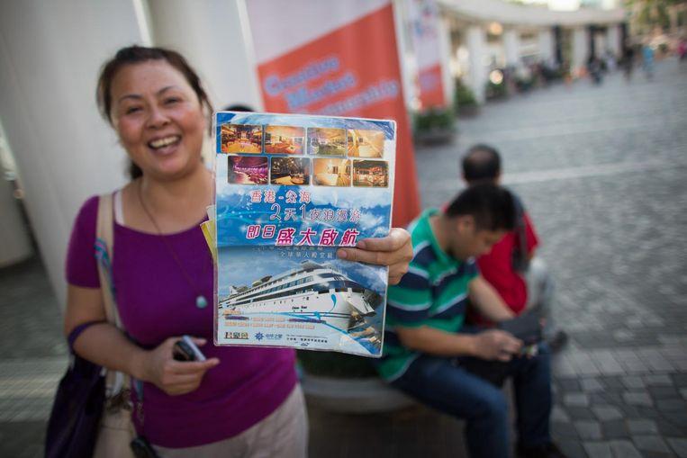 Een vrouw houdt een promotieflyer voor een casinoschip vast. Beeld getty