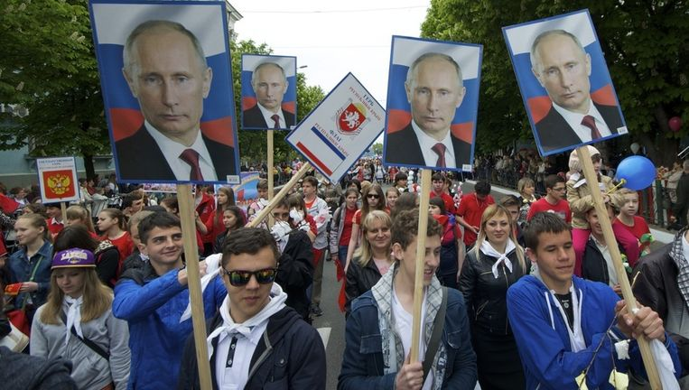 Demonstranten lopen met foto's van de Russische president Vladimir Poetin door Simferopol, de hoofdstad van de Krim.