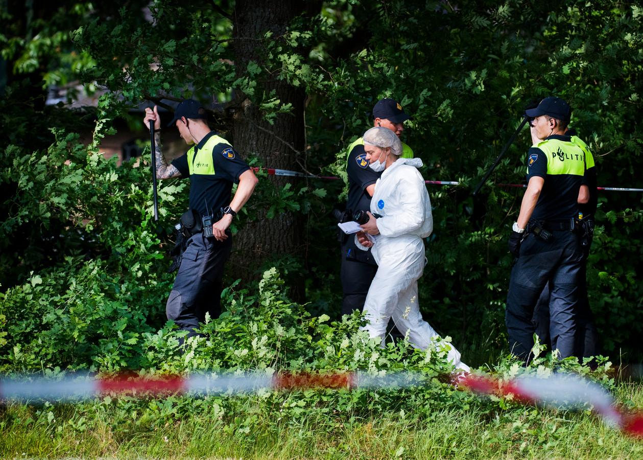 Agenten en forensisch medewerkers doen onderzoek in de buurt van een sloot aan het Emelaarsepad in het buitengebied van Achterveld.