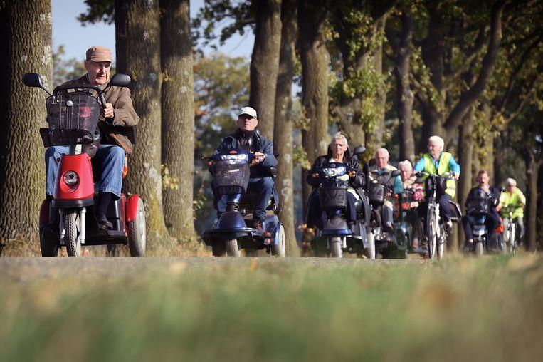 Scootmobieltocht in Asten. Beeld Marcel van den Bergh / de Volkskrant