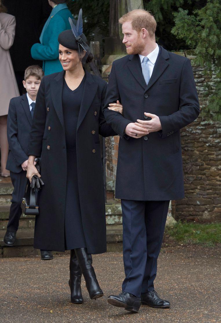 In een donkerblauwe outfit van Victoria Beckham en een hoedje van Philip Treacy.