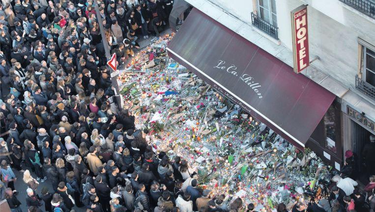 Ondanks het samenscholingsverbod komt zondag een menigte samen bij bar Le Carillon in Parijs, om bloemen te leggen en kaarsen te branden. Beeld epa