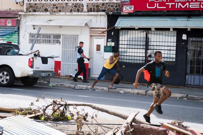 Een Franse soldaat achtervolgt jonge plunderaars op het Franse deel van Sint Maarten.