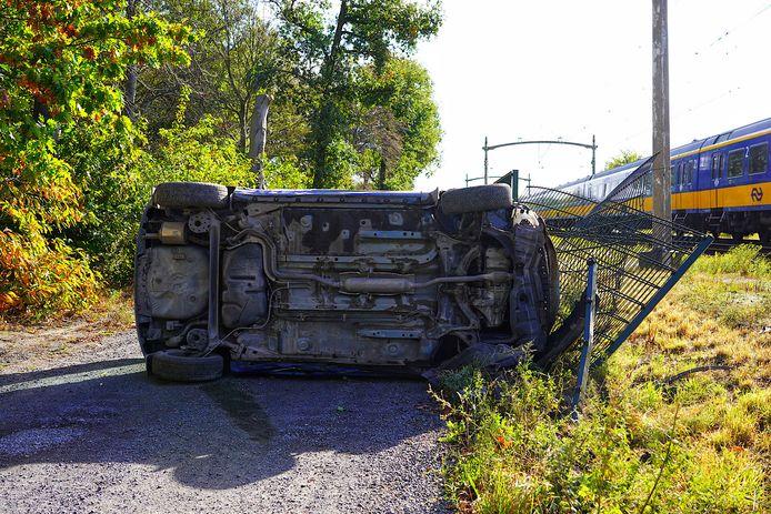 Auto crasht langs het spoor in Dorst.