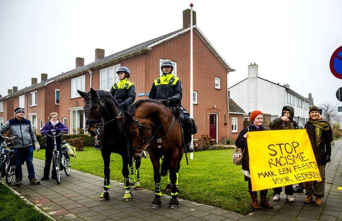 Tegenstanders van Zwarte Piet demonstreren onder het toeziend oog van de politie.