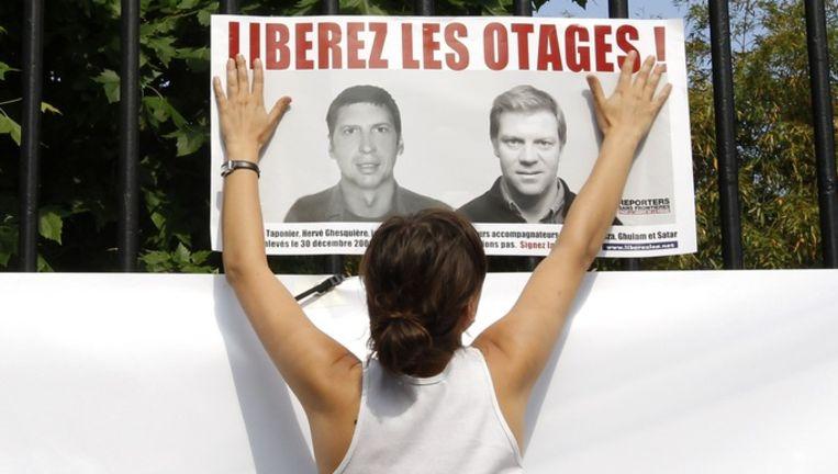 Een vrouw hangt een affiche op als steun voor twee ontvoerde Franse journalisten.
