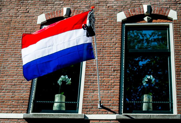 Nederlandse vlag met schooltas van geslaagde scholier.