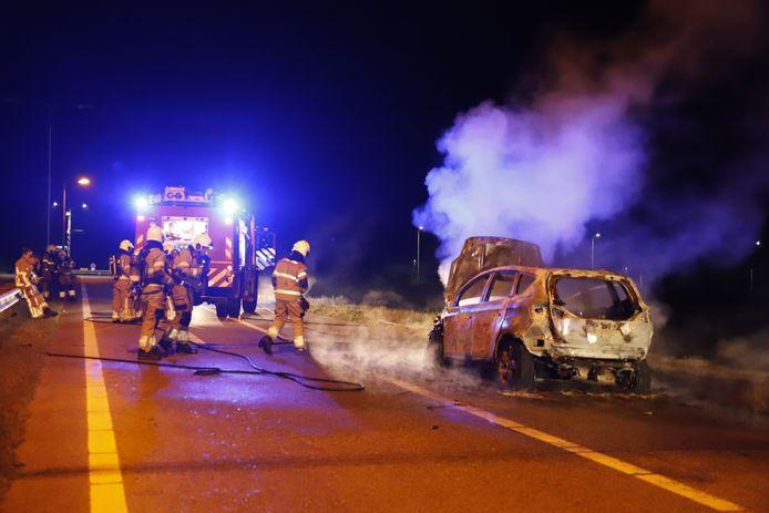 De brandweer blust de brandende auto op de snelweg A73 bij Vierlingsbeek.