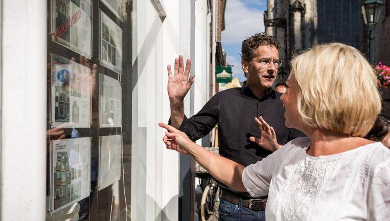 Demissionair ministers Dijsselbloem (Financiën) en Hennis Plasschaert (Defensie) bekijken huizen in de etalage van een Leidse makelaar tijdens het jaarlijkse uitje van het kabinet. Beeld Freek van den Bergh / de Volkskant