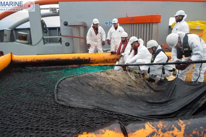 Reddingswerkers proberen een olievlek in te dammen.
