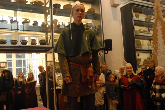 Jongeman, gestoken in kleding uit de tijd van Jheronimus Bosch. Op de achtergrond geeft Anette de Lange tekst en uitleg.