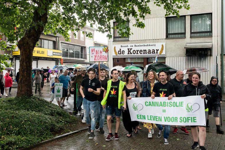 De betogers, met een lachende Karen Damen ondanks de regen, vragen dat minister van Volksgezondheid Maggie De Block cannabisolie legaliseert.