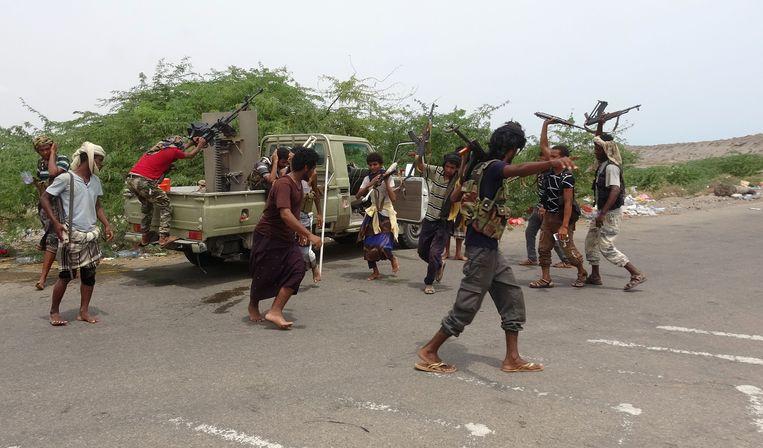 Jemenitische pro-regeringsstrijders dansen op straat na een overwinning op Houthi-rebellen. Beeld AFP
