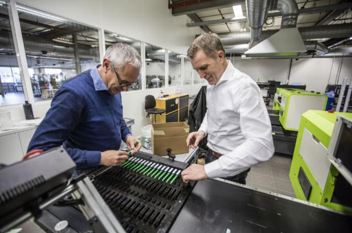 Frans-Jozef Maas (r) en medewerker Theo van der Westen in de productiehal waar zeventig diverse drukmachines de relatiegeschenken bedrukken.