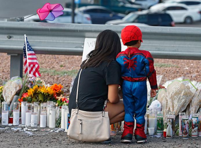 Een vrouw en een jong kind bij een herdenkingsplek